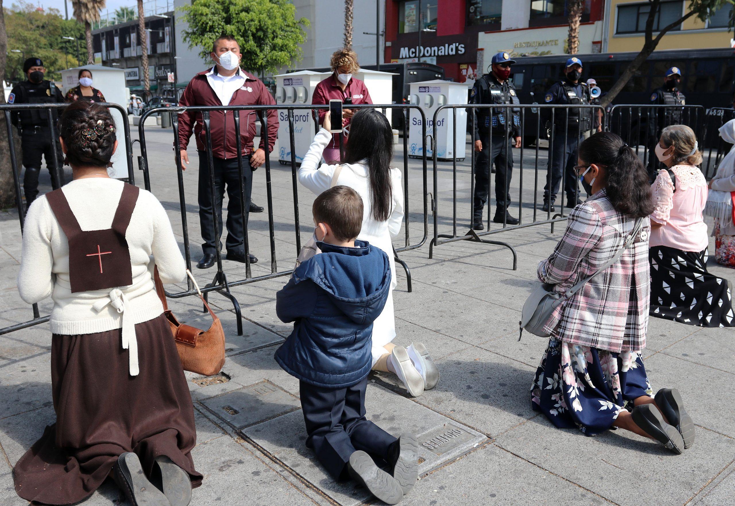 Personas rezan hoy, afuera de la Basílica de Guadalupe de Ciudad de México. EFE/José Pazos