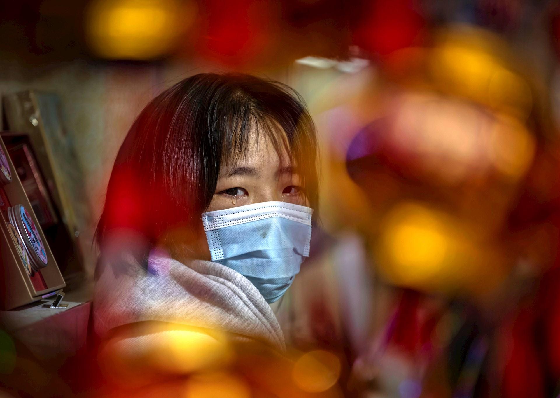 Una mujer con lágrimas en los ojos vende farolillos en su puesto del mercado callejero del jardín Yuyan en Shangái, China. Muchos son los que celebran este año en Shangái el Año Nuevo Lunar debido a la imposibilidad de viajar a sus hogares de origen para pasar las fiestas en familia debido a un nuevo brote que ha obligado a imponer nuevas restricciones de movilidad. Las celebraciones del Año Nuevo Lunar tienen lugar este año entre el 11 y el 26 de febrero. Foto de EFE/ Alex Plavevski.
