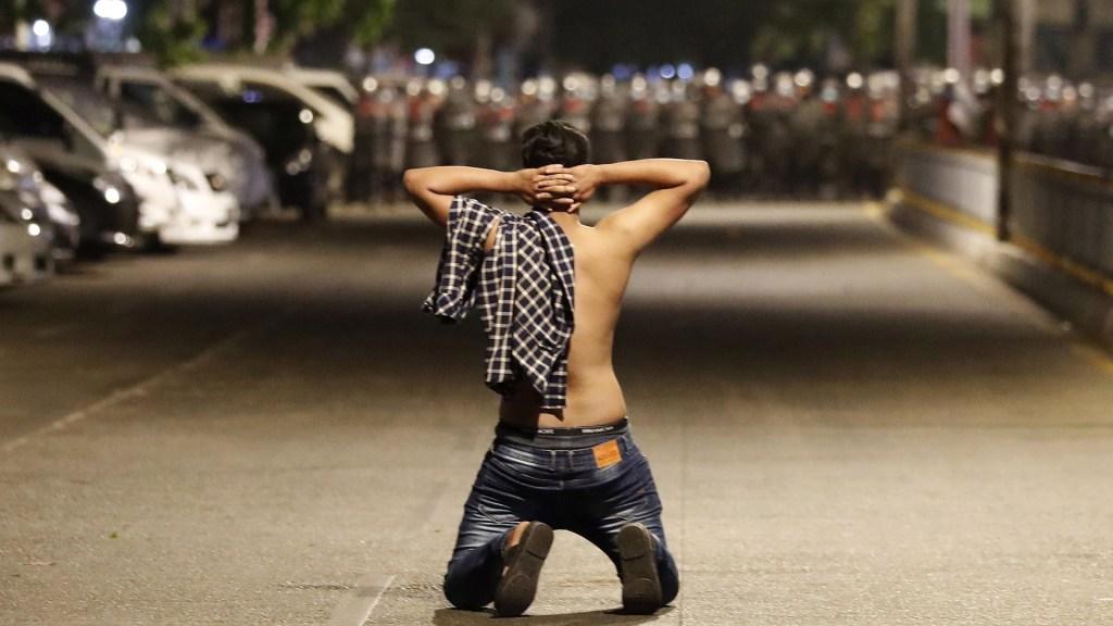 Militares birmanos tomaron por la fuerza control de hospitales, denuncia ONG - Un manifestante se arrodilla mientras protesta contra el golpe militar en Birmania y la policía antidisturbios avanza en una calle de Yangon. Continúan las manifestaciones antigolpistas en medio de los intentos diplomáticos regionales de llegar a una solución a semanas de disturbios causados por el Ejército. Foto de EFE
