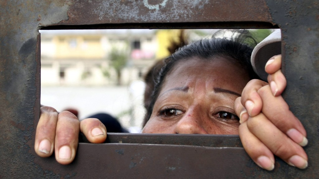 Motines en tres cárceles de Ecuador dejan más de 50 reos muertos - Mujer se asoma por rendija de cárcel en Ecuador. Foto de EFE / Archivo