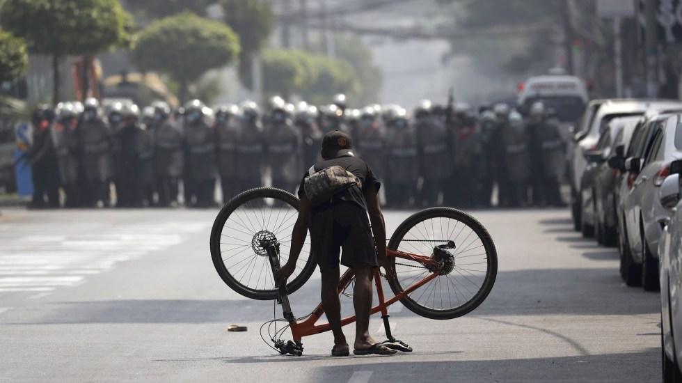"""ONU urge a actuar en Birmania para evitar """"baño de sangre"""" - Un manifestante coloca su bicicleta ante una columna de policías antidisturbios durante una protesta contra el golpe militar en Rangún, este sábado. Foto de EFE/LYNN BO BO."""