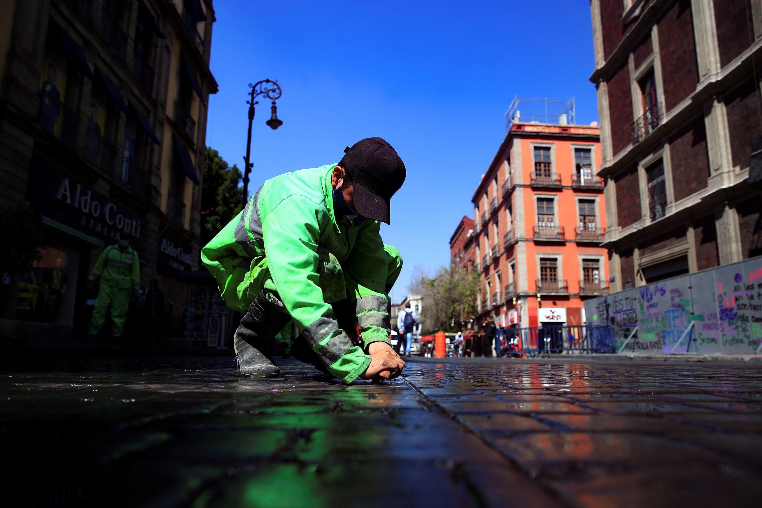 Un hombre de las brigadas de limpieza del gobierno de Ciudad de México restaura los daños ocasionados por el paso de la marcha del 8M, en las principales avenidas de Ciudad de México. Foto de EFE/ Carlos Ramírez.