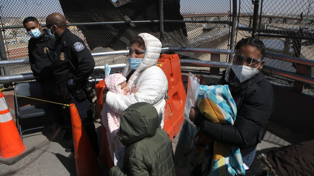 EE.UU. confirma que acabará con detenciones prolongadas de familias migrantes - Miembros de la Organización Internacional por la Migración, escoltan a migrantes centroamericanos, como parte del Protocolo de Protección de Migrantes (MPP), en el puente internacional Paso del Norte en Ciudad Juárez, Chihuahua. Foto de EFE