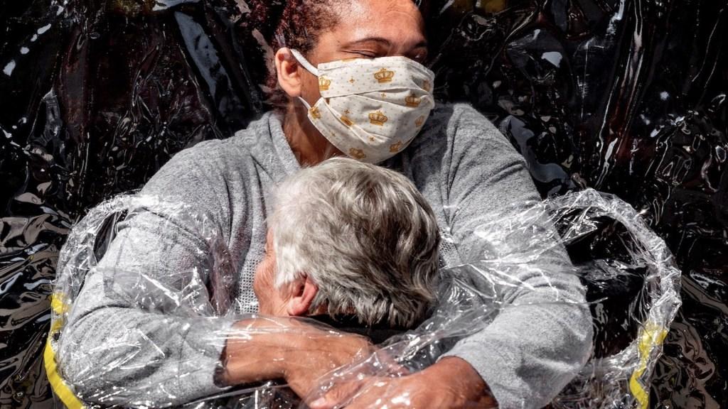 La imagen del primer abrazo entre una mujer de 85 años y una enfermera a través de una cortina de plástico ganó el premio World Press Photo. Foto de EFE