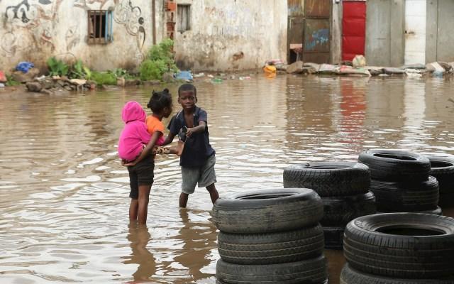 Inundaciones en Luanda - Una niña sostiene a su hermano sobre su espalda en una calle inundada en el barrio de Sambizanga tras las fuertes lluvias que cayeron el 19 de abril y que causaron la muerte de 14 personas e inundaron más de 16 mil casas, Luanda, Angola. Foto de EFE/AMPE ROGÉRIO.