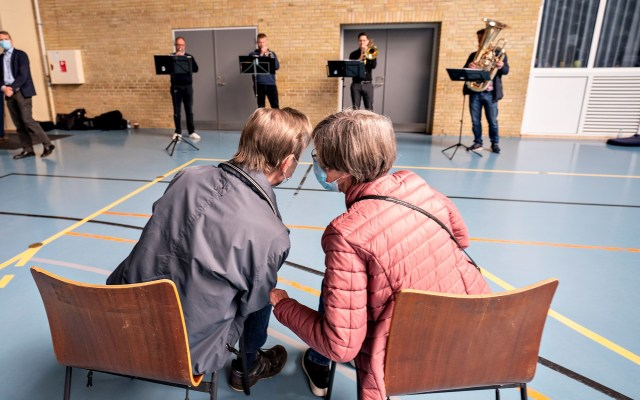 Músicos amenizan la espera para la vacunación - El matrinomio formado por Inga y Erling Halmqvist escucha música en directo mientras esperan su turno para vacunarse contra el coronavirus en un centro de vacunación en Broenderslevhallen, Dinamarca, este martes. La iniciativa de tocar música en el centro de vacunación para amenizar la espera ha tenido tanto éxito, que la región ha firmado un acuerdo de colaboración con el departamento de música de terapia educacional de la universidad de Aalborg para extenderlo a otros centros de vacunación. Foto de EFE/ Henning Bagger DENMARK OUT.
