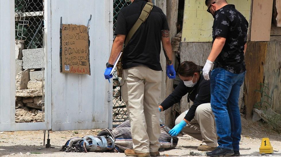 Amenazan con falso cadáver a candidata a diputada local de Ciudad Juárez - Peritos forenses revisan un bulto que simula ser un cadáver frente a la casa de una candidata a diputada local, en Ciudad Juárez, Chihuahua. Foto de EFE