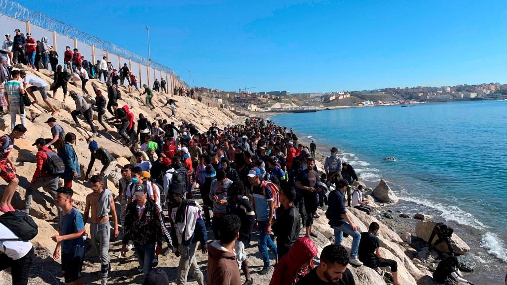 Siete claves para entender la crisis actual entre Marruecos y España - Personas tratan de cruzar la valla fronteriza que separa Fnideq (Castillejos, Marruecos) y Ceuta. Foto de EFE