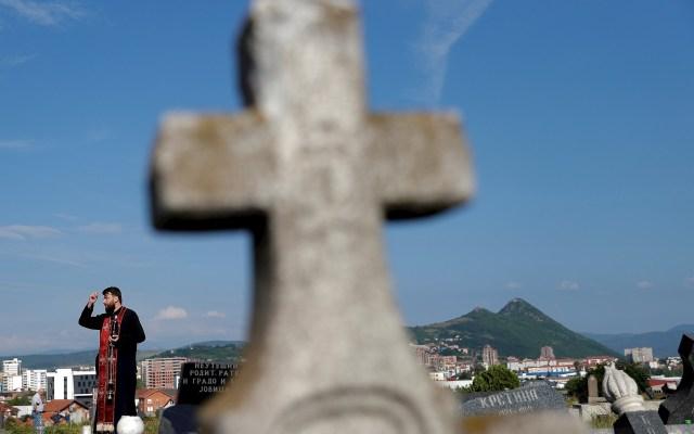 Día de Todos los Santos en Mitrovica - Un sacerdote ortodoxo durante un rezo colectivo con motivo del Día de Todos los Santos celebrado en el cementerio de Mitrovica, Kosovo este sábado. Foto de EFE/ Valdrin Xhemaj.