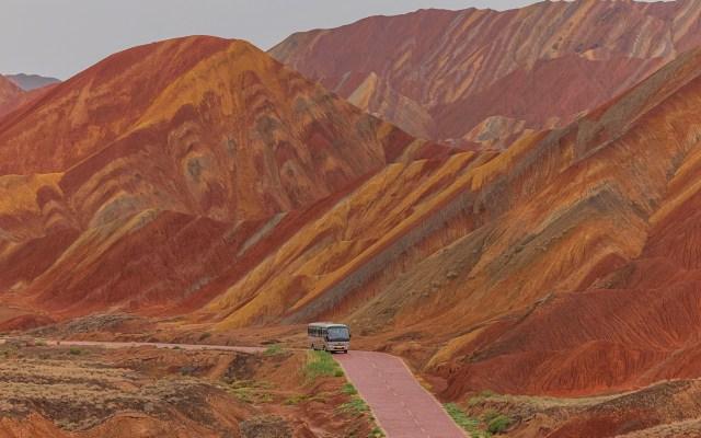 Montañas Arcoíris del Parque geológico nacional Zhangye Danxia - Un autobús circula por una carretera junto a las Montañas Arcoíris del Parque geológico nacional Zhangye Danxia, en China. Las montañas del parque Zhangye Dnxia están reconocidas como Patrimonio Mundial de la UNESCO desde 2009. Foto de EFE