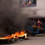 Funeral del asesinado presidente haitiano fue asediado por protestas - Un taximoto con algunas pasajeras pasa junto a una barricada en llamas, durante una jornada de protestas, en Cap-Haitien, Haití. Foto de EFE/ Orlando Barría.
