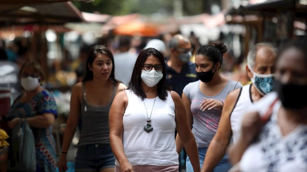 Brasil supera las 574 mil muertes por COVID-19 con la variante Delta avanzando - Personas con cubrebocas, una de las medidas contra COVID-19, caminando por una calle en Vila Isabel, en Rio de Janeiro, Brasil. Foto de EFE/ Fabio Motta/ Archivo
