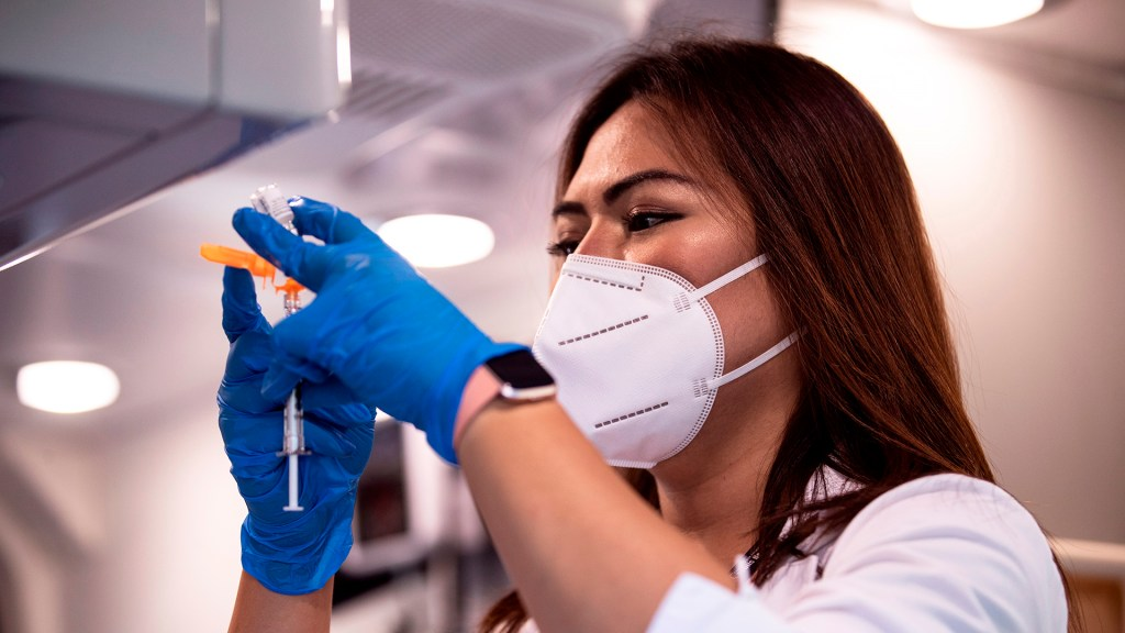 Biden impone vacunación a empleados federales y empresas de más de 100 trabajadores - Enfermera de Estados Unidos prepara dosis de vacuna contra COVID-19