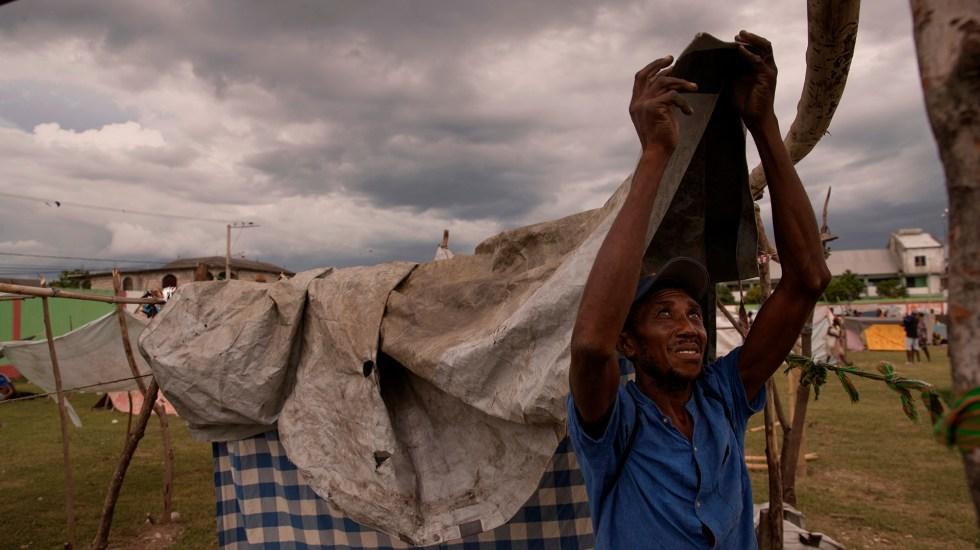 Lluvias azotan la zona más afectada de Haití por sismo - Hombre coloca lonas para protegerse de la lluvia en un campamento improvisado para víctimas del sismo en Haití