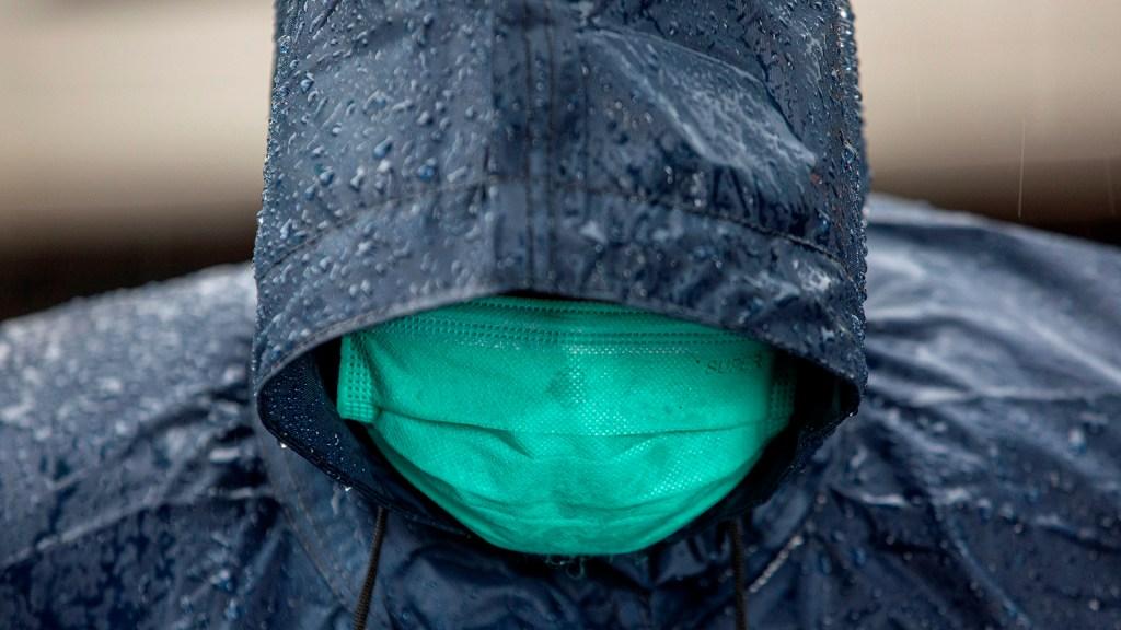 Se forma la tormenta tropical Nicholas en Golfo de México; ocasionará lluvias en cinco estados - Hombre se protege de la lluvia con impermeable