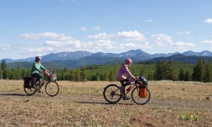 two bicyclists pedaling by on loaded bikes with lofty peaks in the distance