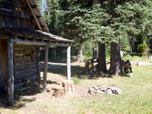 log cabin with a generous porch on the edge of a meadow. bicycles loaded with camping gear leaning against trees and fire ring in the foreground