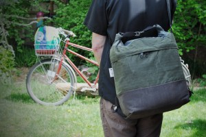 Canvas bag with brown bottom green middle and blue top rolled and connected with 2 metal clips, strapped across persons back with bike in the background on grass