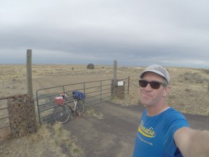 overcast dry grassland with a bicycle leaning against a gate