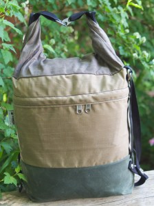 Canvas bag with brown bottom tan middle and brown top rolled and connected with 2 metal clips and black strap dangling, on top of tree trunk