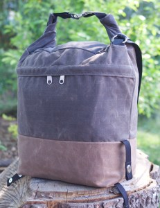 Canvas bag with tan bottom brown middle and brown top rolled and connected with 2 metal clips and black strap dangling, on top of tree trunk