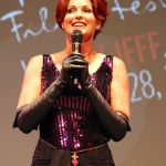 Lorelei Shellist wearing long black gloves, evening gown, speaking on a microphone