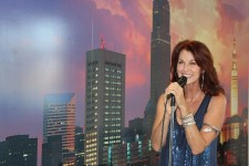 Host Emcee Lorelei Shellist holding microphone, Los Angeles backdrop