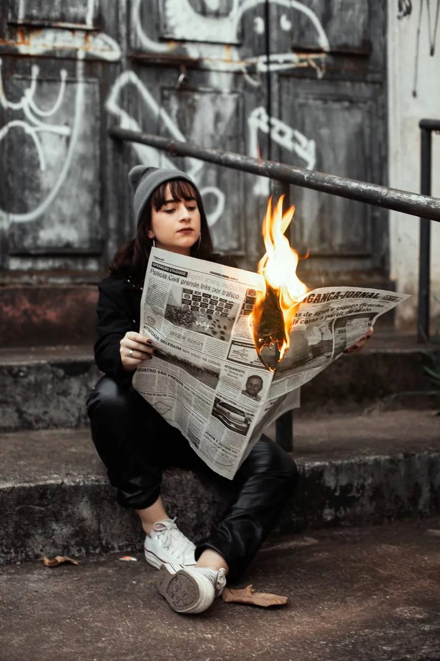 woman holding newspaper while burning - fake news in media monitoring
