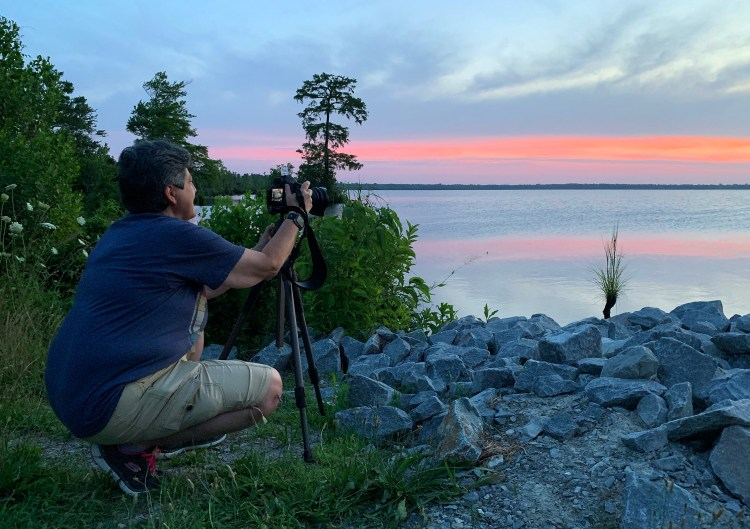 Lori A Cash photographing the sunrise scene at Lake Drummond during the Summer Solstice at the Great Dismal Swamp National Wildlife Refuge in Suffolk, Virginia.