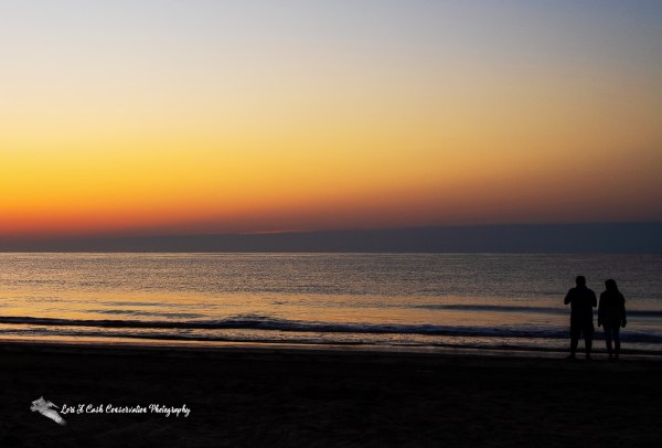 Silhouette of a couple watching the sunrise on a summer morning at Buckroe Beach in Hampton, Virginia.