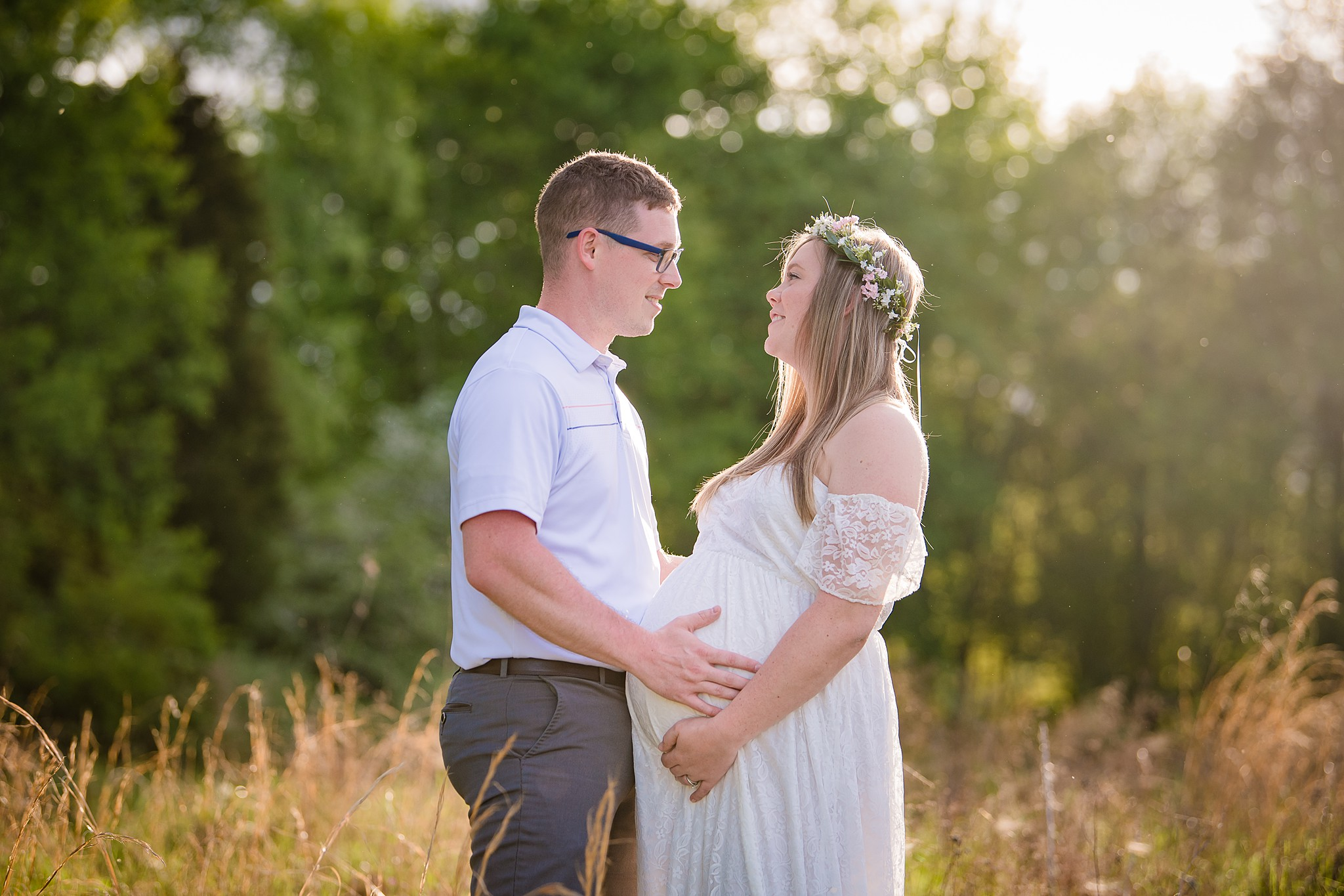 couples maternity session in a field with a flower crown