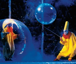 One clown inside a plastic bubble; another clown bounces a large bubble on a stick.