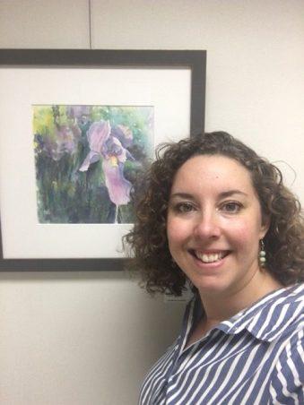 Watercolour artist Candice Leyland stands beside a watercolour painting of an iris (flower).