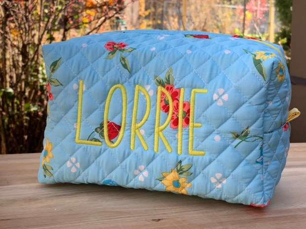 Quilted placemat zipper bag in floral print of teal and orange and exterior scalloped edge
