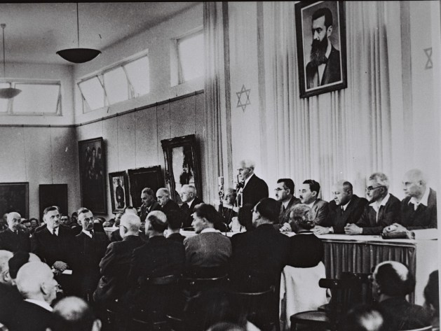 David Ben-Gurion, flanked by the members of his provisional government, reads the Declaration of Independence in the Tel Aviv Museum Hall.