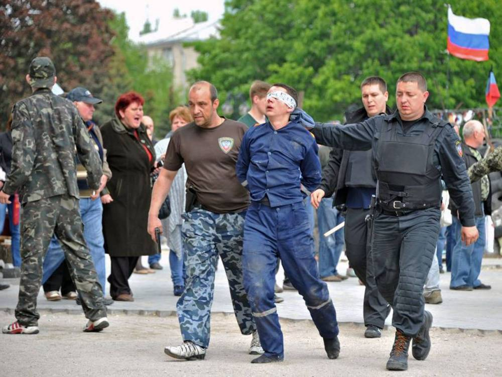 Pro-Russian militants escort a blindfolded man outside the regional state building they seized