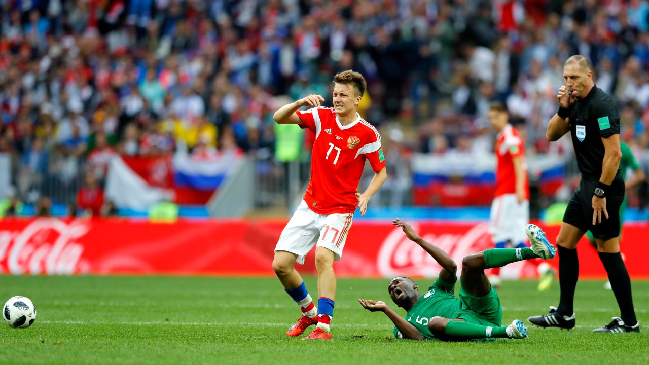 MOSCOW, RUSSIA - JUNE 14: Aleksandr Golovin of Russia foules Omar Othman of Saudi Arabia which leads to Aleksandr Golovin receiving a yellow card during the 2018 FIFA World Cup Russia Group A match between Russia and Saudi Arabia at Luzhniki Stadium on June 14, 2018 in Moscow, Russia.