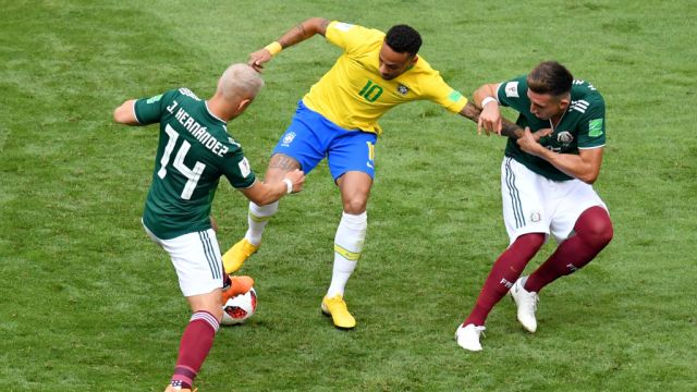 SAMARA, RUSSIA - JULY 02: Neymar Jr of Brazil is challenged by Javier Hernandez of Mexico and Hector Herrera of Mexico during the 2018 FIFA World Cup Russia Round of 16 match between Brazil and Mexico at Samara Arena on July 2, 2018 in Samara, Russia.