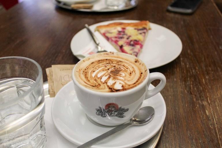 Café en el centro. Un pedazo de tarta en segundo plano.