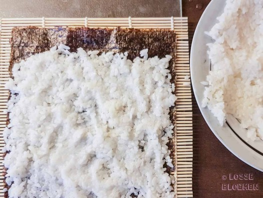 Stap 3 rijst op norivel doen met natte handen lossebloemen. nl hoe maak ik plantaardige sushi stappenplan