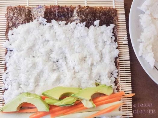Stap 4 gewenste groente op norivel doen met natte handen lossebloemen. nl hoe maak ik plantaardige sushi stappenplan