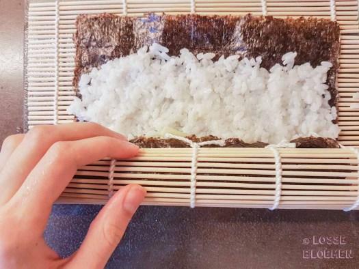Stap 5 rijst met gewenste groente rollen met bamboematje doen met natte handen lossebloemen. nl hoe maak ik plantaardige sushi stappenplan