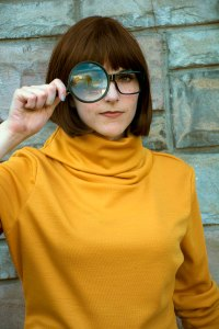 Lossien as Velma, wearing a yellow sweater, a brown bob wig, and glasses, holding a magnifying glass over one eye.
