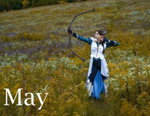 Lossien dressed as Vex. She is in a white coat with a blue undershirt and pants, and white greaves. She has long brown hair in a side braid and is holding a bow at the ready, with an arrow, ready to fire. She is standing in a field of flowers. The word 'May' appears in the bottom left.