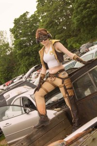 Lossien standing on the bed of a truck in a junkyard, wearing Junker D.Va. She has on a short brown wig, a white cropped shirt, tan pants with brown spats, and a brown vest.