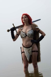 Lossien with red hair in a scalemaille bikini, and a fur back piece. She is wearing black gloves, and standing in water, while holding a sword over her shoulder.