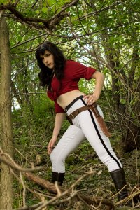 Lossien as Hannah Dundee, wearing a curly brown wig, a cropped red shirt, and white pants with a stripe down the side. Standing in the woods.
