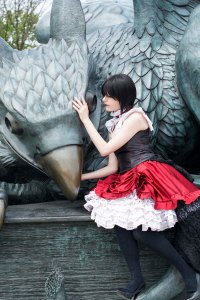 Wearing a black short wig and corset, with a red overskirt and white underskirt, Lossien is holding the beak of a large gryphon statue.