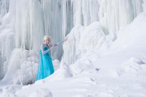 Lossien as Elsa, in blue with a blonde wig, standing in front of a frozen waterfall.