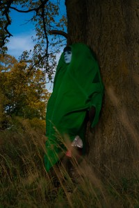 Lossien in a giant leaf costume, leaning against the trunk of a tree. She has blue skin as Jester, and the costume is green with a brown stem coming out the top.